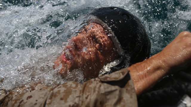 A Marine assigned to Company A, 1st Marine Reconnaissance Battalion, 1st Marine Division, holds onto the side of a combat rubber raiding craft after completing a parachute jump into the ocean at Marine Corps Base Camp Pendleton, California, July 14, 2015.  The Marines and Sailors conducted low-level static-line parachute operations with intentional water landings to make insertions, where other means such as boats or high-altitude parachute jumps may not be available.
