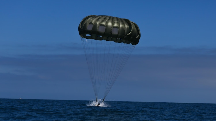 A Marine assigned to Company A, 1st Marine Reconnaissance Battalion, 1st Marine Division, performs a parachute jump into the ocean at Marine Corps Base Camp Pendleton, California, July 14, 2015.  The Marines and Sailors conducted low-level static-line parachute operations with intentional water landings to make insertions, where other means such as boats or high-altitude parachute jumps may not be available.
