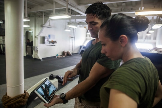 U.S. Marine Sgt. Sean Bernstein, left, shows Lance Cpl. Chevon Ferrel a video of a speed reload aboard the amphibious assault ship USS Essex (LHD 2). Bernstein is a member of the 15th Marine Expeditionary Unit's Maritime Raid Force and Ferrel is an ammunition technician with Combat Logistics Battalion 15, 15th MEU. The Marines watch videos of themselves practicing drills to correct deficiencies they may not otherwise notice. The 15th MEU is embarked on the Essex Amphibious Ready Group and deployed to maintain regional security in the U.S. 5th Fleet area of operations.