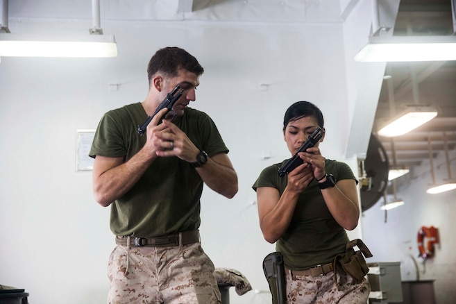 U.S. Marine Sgt. Erik Maehler, left, demonstrates loading a M9 Beretta pistol to Hospital Corpsman 1st Class Sunshine Padilla aboard the amphibious assault ship USS Essex (LHD 2). Maehler is a member of the 15th Marine Expeditionary Unit's Maritime Raid Force and Padilla is a hospital corpsman with Marine Medium Tiltrotor Squadron 161 (Reinforced), 15th MEU. The Marines practice marksmanship fundamentals dry to ensure safety and accuracy when shooting. The 15th MEU is embarked on the Essex Amphibious Ready Group and deployed to maintain regional security in the U.S. 5th Fleet area of operations.