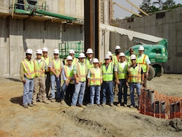 Members of Fort Benning's Project Delivery Team coalesce after the first piece of structural steel was placed at the site April 9, 2012.