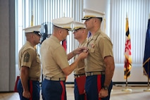 U.S. Marine Corps Col. John A. Bolt, the commanding officer of 4th Marine Corps Recruiting District, awards a Meritorious Service Medal to Maj. Jason C. Copeland, the incoming commanding officer of Recruiting Station Baltimore, during a change of command ceremony at Fort George G. Meade, Maryland, June 18, 2015. Copeland, a native of Roswell, New Mexico, was awarded the medal for outstanding meritorious service while serving as the commanding officer of Company G and as the operations officer for 2nd Battalion, 5th Marine Regiment. (U.S. Marine Corps photo by Cpl. Tyler Birky/Released)