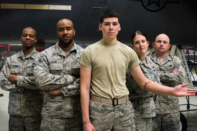 Airmen from the 366th Equipment Maintenance Squadron at Mountain Home Air Force Base, Idaho, stand behind Airman 1st Class Saul Vasquez (center) May 14, 2015. On April 2, 2015, Vasquez tore his radial artery inside the belly of an F-15E Strike Eagle. Without the quick response and self-aid and buddy care training of his fellow Airmen, he may not be alive today. (U.S. Air Force photo/Airman Connor J. Marth)