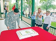 Col. Cyrulik, cuts the celebratory cake with a cavalry saber.