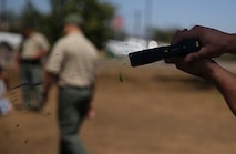 Military police and civilian law enforcement officers with the Marine Corps Air Station Miramar Provost Marshals Office (PMO) fire the Taser X26 during their annual Taser training aboard MCAS Miramar, California, July 15. The training helped familiarize the law enforcement personnel with standardized procedures for employing nonlethal weapons. (U.S. Marine Corps photo by Sgt. Brian Marion/Released)