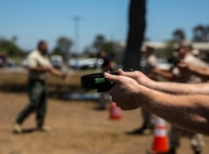 Military police and civilian law enforcement officers with the Marine Corps Air Station Miramar Provost Marshals Office (PMO) practice drawing and aiming the Taser X26 during annual Taser training aboard MCAS Miramar, California, July 15. The training helped familiarize the law enforcement personnel with standardized procedures for employing the weapon. (U.S. Marine Corps photo by Sgt. Brian Marion/Released)