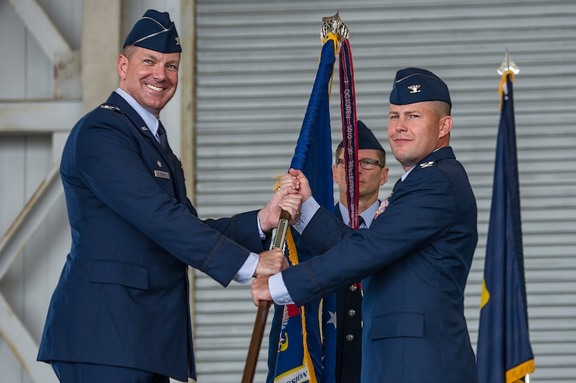 Colonel Robert Lyman (left), Joint Base Charleston commander, passes the 628th Mission Support Group guidon to incoming commander, Col. Richard Mathews (right), during the 628th MSG change of command, July 17, 2015 at Joint Base Charleston, SC.  Matthews assumed command of the 628th MSG from Col. Michael Mongold during the ceremony. Matthews comes to JB Charleston from Air Mobility Command at Scott Air Force Base, Ill,, where he was chief, Engineering Division Direcotrate of Instllations and Mission Support. Mongold is headed to the Air Force Personnel Center at Joint Base San Antonio – Randlolph, Texas, where he will serve as the chief of the Air Expeditionary Forces Operations Squadron.  (U.S. Air Force photo/ Airman 1st Class Thomas T. Charlton)