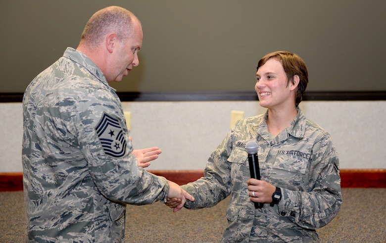 U.S. Air Force Chief Master Sgt. James W. Hotaling, Air National Guard command chief, recognizes Airman 1st Class Willow Gragg, 116th Security Forces Squadron, Georgia Air National Guard, as being one of the 116th Air Control Wing's newest Guardsman during an enlisted all call at Robins Air Force Base, Ga., July 16, 2015. During his visit, Hotaling conducted two town hall style meetings and met with key enlisted leadership councils and Airmen resiliency representatives. His time with the Airmen focused on sharing his message of a renewed commitment to the profession of arms, health of the force, and recognition of our Airmen and accomplishments. The visit offered the opportunity for Airmen in the wing to meet their top leader, share their concerns and gain perspective from the national level. (U.S. Air National Guard photo by Tech. Sgt. Regina Young/Released)