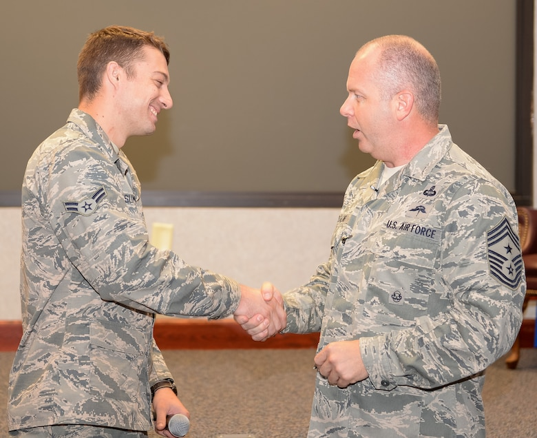 U.S. Air Force Chief Master Sgt. James W. Hotaling, Air National Guard command chief, recognizes Airman 1st Class Caleb Summers, 116th Maintenance Squadron, Georgia Air National Guard, as being one of the 116th Air Control Wing's newest Guardsman during an enlisted all call at Robins Air Force Base, Ga., July 16, 2015. During his visit, Hotaling conducted two town hall style meetings and met with key enlisted leadership councils and Airmen resiliency representatives. His time with the Airmen focused on sharing his message of a renewed commitment to the profession of arms, health of the force, and recognition of our Airmen and accomplishments. The visit offered the opportunity for Airmen in the wing to meet their top leader, share their concerns and gain perspective from the national level. (U.S. Air National Guard photo by Tech. Sgt. Regina Young/Released)