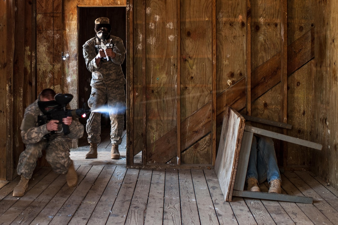 A Soldier with the U.S. Army Reserve 312th Engineer Company, based in Duluth, Minn., fires his M4 rifle paintball gun while an opposing force member hides behind a table during urban operations training and building clearing procedures, April 18, 2015, at Camp Ripley, Minn. The 312th has seen a turnaround in its retention and recruiting based on an atmosphere of caring about each Soldier and their families while providing meaningful and innovative training during each battle assembly. (U.S. Army photo by Timothy L. Hale/Released)