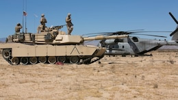 Marines of Company A, 1st Tank Battalion, prepare an M1A1 Abrams tank to receive fuel from a CH-53 Super Stallion with Marine Heavy Helicopter Squadron 465 at Acorn Training Area, July 16, 2015. Each tank has the capability to hold 500 gallons of fuel.