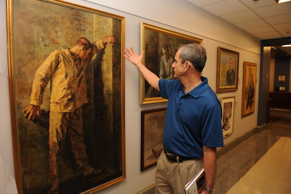 Retired Col. Leon Ellis visits the Air Force prisoner of war tribute section in the Pentagon July 16, 2015. Ellis, a Vietnam War POW, admired a painting by Maxine McCaffrey. The painting portrays realistic features about being a captive in a prison camp. (U.S. Air Force photo/Staff Sgt. Whitney Stanfield)