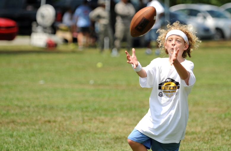 A young athlete lines up to snag a pass during a National Football League ProCamp, July 16, 2015, at Seymour Johnson Air Force Base, N.C. ProCamps are held all over the U.S. and internationally, to give children once-in-a-lifetime skill training with professional athletes. (U.S. Air Force photo/Senior Airman Ashley J. Thum)
