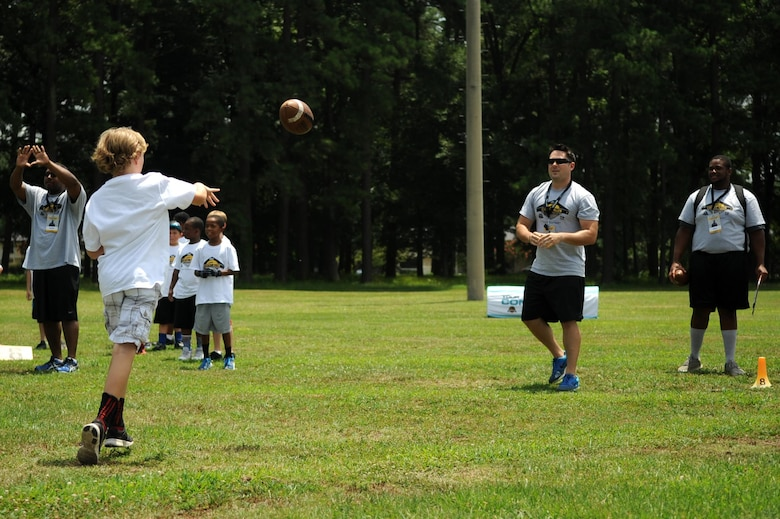 A young athlete practices passing drills with a volunteer coach during a National Football League ProCamp, July 16, 2015, at Seymour Johnson Air Force Base, N.C. More than 100 children turned out for the two-day camp. (U.S. Air Force photo/Senior Airman Ashley J. Thum)