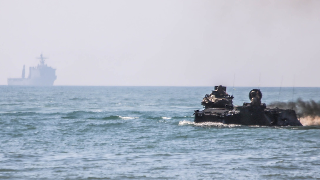 Marines with 2nd Assault Amphibious Battalion, 2nd Marine Division, drive assault amphibious vehicles to shore from the USS Whidbey Island during amphibious training operations in the waters off the coast of Camp Lejeune, N.C., July 16, 2015. The exercise allowed Marines to fulfill their required ship operations and gave sailors aboard the Whidbey Island the opportunity to work with Marines during their own amphibious training.