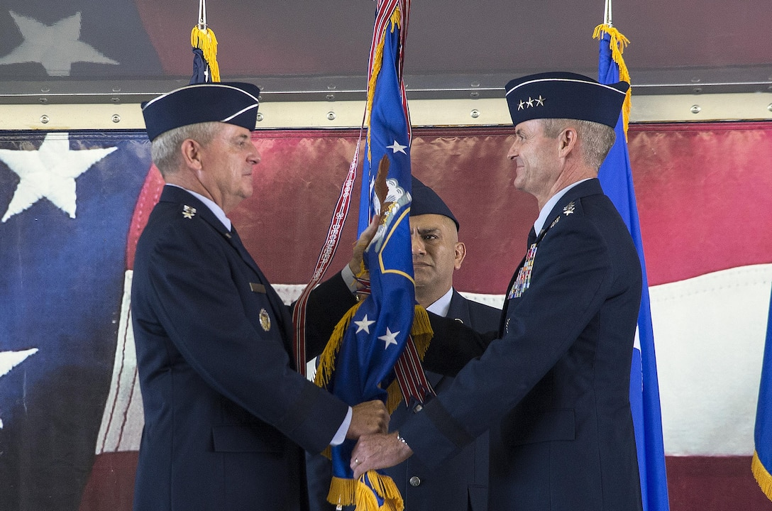 JOINT BASE SAN ANTONIO-RANDOLPH, Texas -- Air Force Chief of Staff Gen. Mark A. Welsh III (left) passes the Air Education and Training Command guidon to Lt. Gen. Darryl Roberson, commander of AETC, during a change of command ceremony at Joint Base San Antonio-Randolph, Texas, July 21, 2015. The change of command ceremony represents the formal passing of responsibility, authority and accountability of command from one officer to another. (U.S. Air Force photo by Johnny Saldivar)