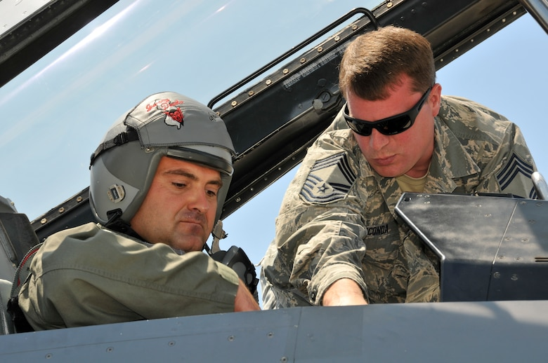 U.S. Air Force Chief Master Sgt. Jason Gioconda, aircrew flight equipment superintendent with the 177th Fighter Wing of the New Jersey Air National Guard, goes over egress procedures with Bulgarian air force MiG-29 pilot Capt. Ivan Dinkov prior to his familiarization flight in an F-16D Fighting Falcon at Graf Ignatievo Air Base, Bulgaria on July 15, 2015. Gioconda and Dinkov are participating in Thracian Star, a bilateral training exercise to enhance interoperability with the Bulgarian air force and to bolster readiness to conduct combined air operations. Pilots from both countries benefit from familiarization flights in each other's fighter jets. (U.S. Air National Guard photo by Master Sgt. Andrew J. Moseley/Released)
