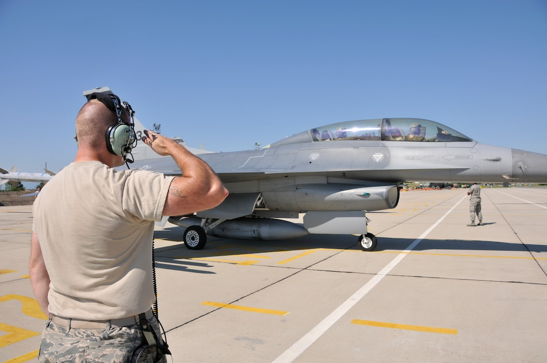 U.S. Air Force Senior Airman Mark Cavanaugh, crew chief with the 177th Fighter Wing of the New Jersey Air National Guard, salutes the pilot of an F-16D Fighting Falcon as it taxis for takeoff at Graf Ignatievo Air Base, Bulgaria July 15, 2015. The 177th FW is participating in Thracian Star, a bilateral training exercise to enhance interoperability with the Bulgarian air force and to bolster readiness to conduct combined air operations. (U.S. Air National Guard photo by Master Sgt. Andrew J. Moseley/Released)