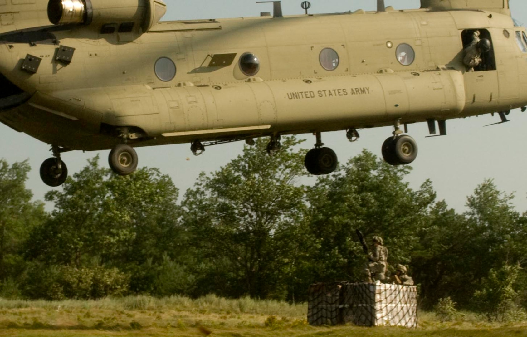 Two New York Army National Guard Soldiers from Company A, 427th Brigade Support Battalion, prepare to attach a sling-load to a CH-47 Chinook helicopter piloted by aviators from Company B, 3rd Battalion, 126th Aviation, July 19, 2015. The Soldiers, part of the 27th IBCT are at Fort Drum participating in an Exportable Combat Training Capability exercise in preparation of the Brigade's rotation at the Joint Readiness Training Center at Fort Polk, La., scheduled for 2016.