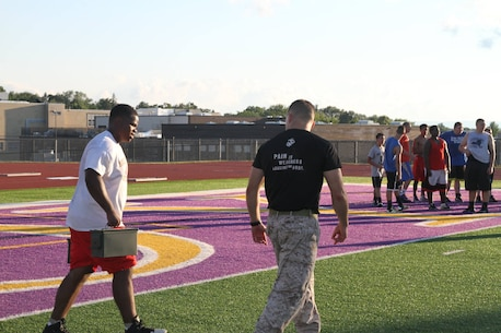 Marines with Recruiting Station Albany, NY, motivate athletes of the Troy High School football team through a circuit course at the school's football field in Troy, NY, Tuesday, July 21, 2015. The circuit course was the concluding exercise in a leadership seminar the Marines conducted for the football team.