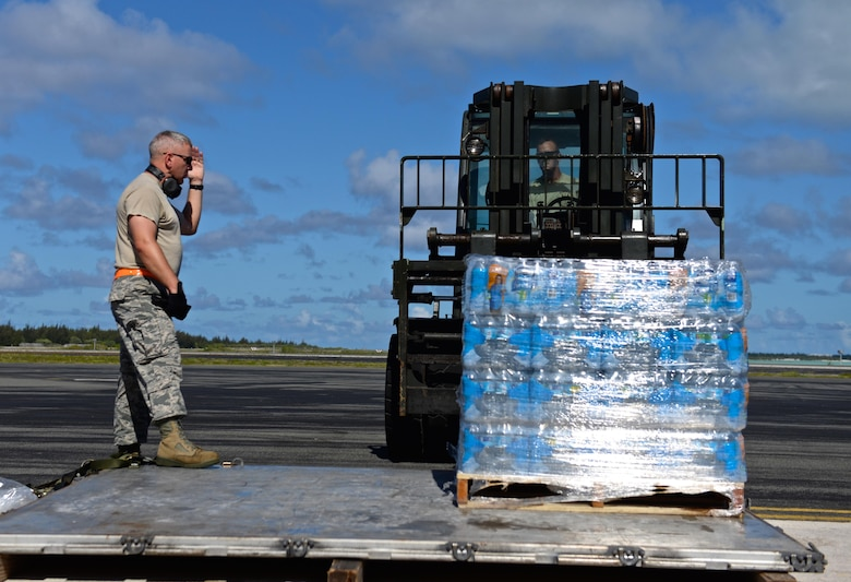 U.S. Air Force Master Sgt. Iain Morrison, 36th Contingency Response Group superintendent of operations, plans and programs, guides Tech. Sgt. Randy Walgren, 36th Mobility Response Squadron NCO in charge of aerial port operations, in moving drinking water rations, July 20, 2015, Wake Island Airfield. The 36th CRG deployed from Andersen Air Force Base, Guam, to assist in airfield storm recovery efforts after the small atoll was evacuated a few days earlier for Typhoon Halola. (U.S. Air Force photo by Senior Airman Alexander W. Riedel/Released)