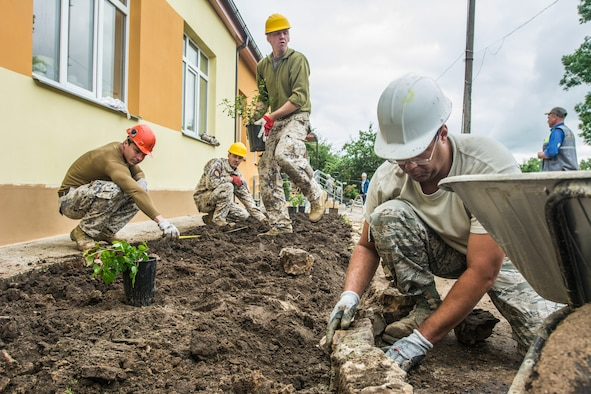 U.S. Air Force Staff Sgt. Matthew Mays, an engineering assistant with the 139th Civil Engineer Squadron, Missouri Air National Guard works on landscaping alongside soldiers from the Latvian National Armed Forces during the reconstruction of the Naujenu Orphanage near Daugavpils, Latvia, July 20, 2015.  The 139th CE was participating in the Humanitarian Civic Assistance project that pairs units training requirements with humanitarian needs.  (U.S. Air National Guard photo by Senior Airman Patrick P. Evenson/Released)