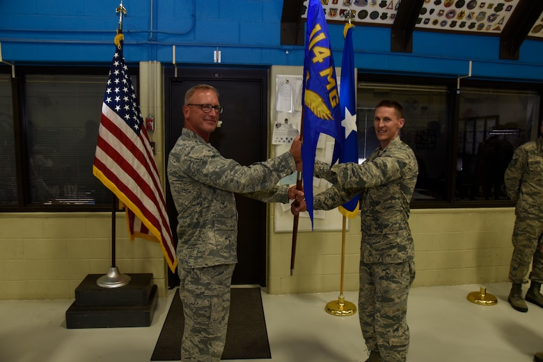 Col. Joel Degroot, 114th Maintenance Group commander, passes the 114th Maintenance Squadron (MXS) guidon to Lt. Col. Travis Boltjes, the incoming 114th MXS commander, during a change of command ceremony at Joe Foss Field, S.D., July 12, 2015. The primary purpose of a change of command ceremony is to allow subordinates to witness the formality of command change from one officer to another. The 114th MXS is the largest squadron on base with almost 250 Airmen. (National Guard photo by Staff. Sgt. Luke Olson/Released)