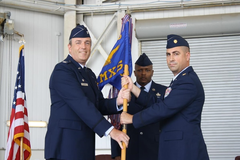 Colonel Brian Peters, 437th Maintenance Group commander, passes the guidon to Maj. Robert Ryder, the new 437th Aircraft Maintenance Squadron commander during an assumption of command ceremony held at Joint Base Charleston, S.C., July 22, 2015. Ryder comes to JB Charleston from MacDill Air Force Base, Fla., where he was the 6th Aircraft Maintenance Squadron commander. Lt. Col. Adam DiGerolamo, the former 437th AMXS commander departed JB Charleston in June 2015 and is now the 379th Expeditionary Aircraft Maintenance Squadron commander at Al Udeid Air Base. (Courtesy photo / 437th Aircraft Maintenance Squadron)
