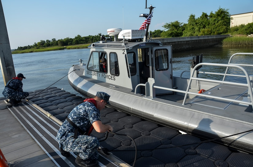 (Left) Aviation Boatswain's Mate Fuels Curtis Clausen and Machinist Mate 2nd Class Kevin Labencki, from the 628th Logistics Readiness Squadron Port Operations, dock a Harbor Security Boat, July 21, 2015 at Joint Base Charleston – Weapons Station, S.C. The 628th LRS Port Operations received two new 27-foot Harbor Security Boats to replace older watercraft. These HSBs are highly maneuverable, welded aluminum boats powered by 150-horse powered outboard engines. The 628th LRS currently has six boats in their inventory. (U.S. Air Force photo/Staff Sgt. AJ Hyatt)