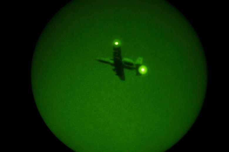 A 354th Expeditionary Fighter Squadron A-10C Thunderbolt II aircraft flies overhead at night during an austere landing training exercise at Nowe Miasto, Poland, July 20, 2015. During night hours, pilots will use night vision goggles to land on an unimproved surface when no light is available. (U.S. Air Force photo by Airman 1st Class Luke Kitterman/Released)