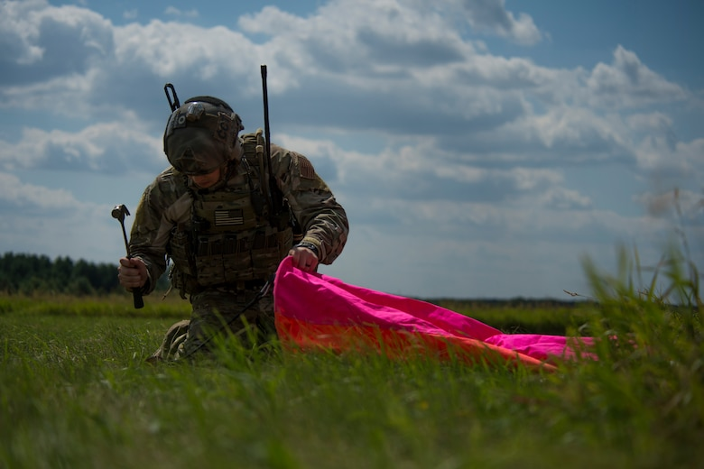 A 321st Special Tactics Squadron combat controller hammers a distance marker into place before the start of an austere landing training exercise at Nowe Miasto, Poland, July 20, 2015. The colorful markers are used as a reference point to aid pilots when landing on unimproved surfaces. (U.S. Air Force photo by Airman 1st Class Luke Kitterman/Released)