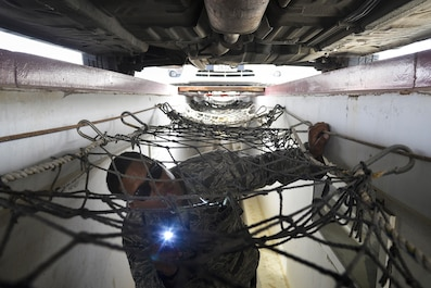 Senior Airman Alema searches the bottom of a vehicle for contraband and explosives at an undisclosed location in Southwest Asia July 13, 2015. Airman Alema is a security forces member assigned to the 380th Expeditionary Security Forces Squadron, vehicle search area. (U.S. Air Force photo/Tech. Sgt. Christopher Boitz)