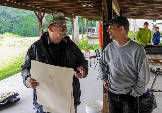 Lt. Col. Mark Gould (right) hands in his target and talks to instructor George Harris during a training class in New Freedom, Pa., June 26, 2015. Gould, a foreign liaison officer for the Defense Intelligence Agency's Office of Partner Engagement at the Pentagon, has been involved in competitive shooting for the past 23 years and has been a member of the Air Force International Rifle Team for 17 years. Harris, a former manager of National Rifle Association rifle competitions for 26 years, instructed the two-day course. (U.S. Air Force photo/Staff Sgt. Christopher Gross)