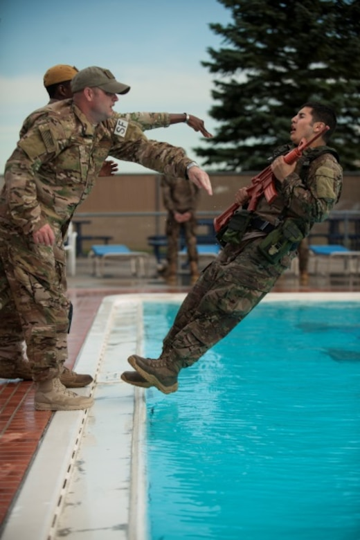 Master Sgt. Todd Boren and Staff Sgt. Gregory Carter, 5th Security Forces Squadron ranger assessment course cadre members, push Staff Sgt. Miguel Garcia, a 5th SFS member, into the pool for a water confidence exercise during pre-ranger training at Minot Air Force Base, N.D., July 15, 2015. To pass the course, Airmen like Garcia are required to complete a Ranger Physical Assessment, combat water survival assessment, 12-mile foot march, and day and night combined land navigation. (U.S. Air Force photo/Airman 1st Class Christian Sullivan)