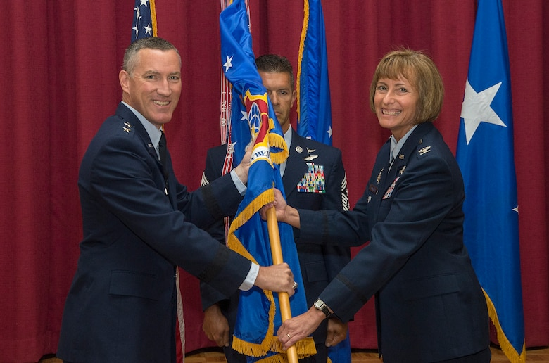 Maj. Gen. Ed Burke, 24th Air Force commander, passes the wing guidon to Col. Michelle Hayworth during the 688th Cyberspace Wing's change of command ceremony at Joint Base San Antonio-Lackland, Texas, July 17. Before coming to command the 688th Cyberspace Wing, Hayworth was the Communications Director for Headquarters U.S. Air Forces in Europe-Air Forces Africa. (U.S. Air Force photo by Johnny Saldivar/Released)