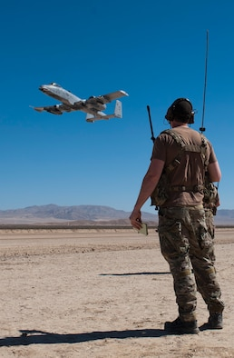 An Airman assigned to the 22nd Special Tactics Squadron, Joint Base Lewis-McChord, Wash., observes as an A-10 Thunderbolt II circle before landing in support of Green Flag West 15-08.5 on the National Training Center range at Fort Irwin, Calif., July 16, 2015. This marked the first time an A-10 landed on the range. (U.S. Air Force photo by Airman 1st Class Mikaley Towle)