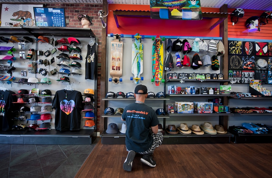 Retired Tech. Sgt. Alfredo Sibucao Jr. organizes a hat display inside his retail store in Las Vegas, June 22, 2015. Sibucao, who attended middle and high school in Las Vegas, spent a combined 13 years between Nellis and Creech Air Force Bases before retiring and opening his business in Las Vegas. (U.S. Air Force photo by Staff Sgt. Siuta B. Ika)