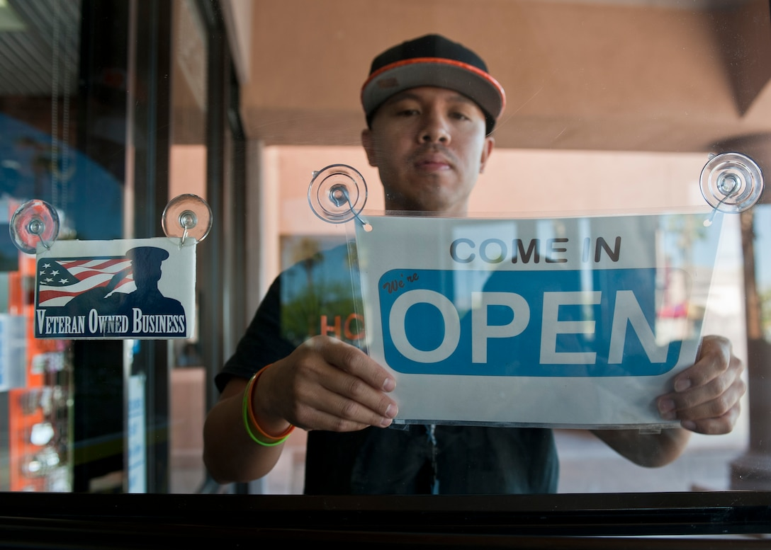 Retired Tech. Sgt. Alfredo Sibucao Jr. flips the open sign to his retail store in Las Vegas, June 22, 2015. Sibucao retired from the Air Force in 2014 and now owns and operates a small business in Las Vegas. (U.S. Air Force photo by Staff Sgt. Siuta B. Ika)