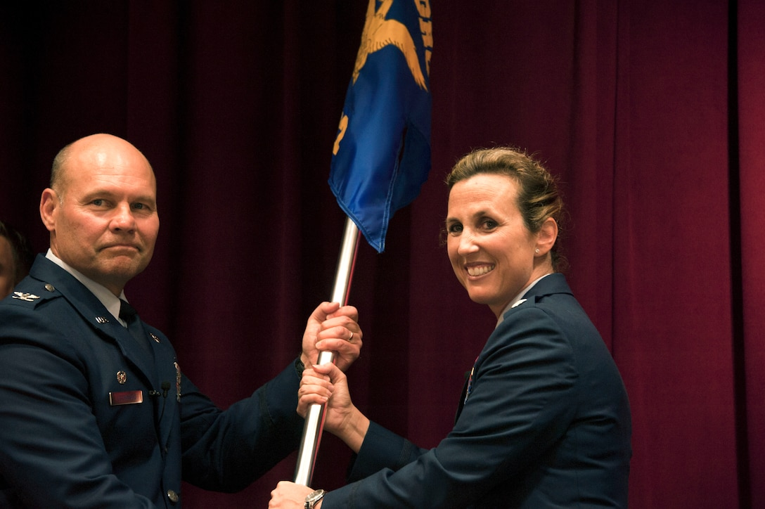 Col. Scott Lockwood, commander, Air Force Officer Training School, transfers command of Detachment 12 to Lt. Col. Loralie Rasmussen during a change of command ceremony July 16, 2015, Maxwell Air Force Base, Alabama. Rasmussen took command of the detachment from her husband, Lt. Col. Reid Rasmussen, who is attending Air War College here. (U.S. Air Force photo by Airman 1st Class Alexa Culbert)