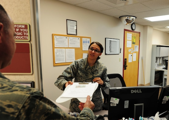 Staff Sgt. Allison Lai, 319th Medical Operations Squadron NCO-in-charge of dental support, hands paperwork to a customer July 21, 2015, at the Medical Treatment Facility on Grand Forks Air Force Base, N.D. Lai was selected as the Warrior of the Week for the fourth week of July. (U.S. Air Force photo by Airman 1st Class Ryan Sparks/released)