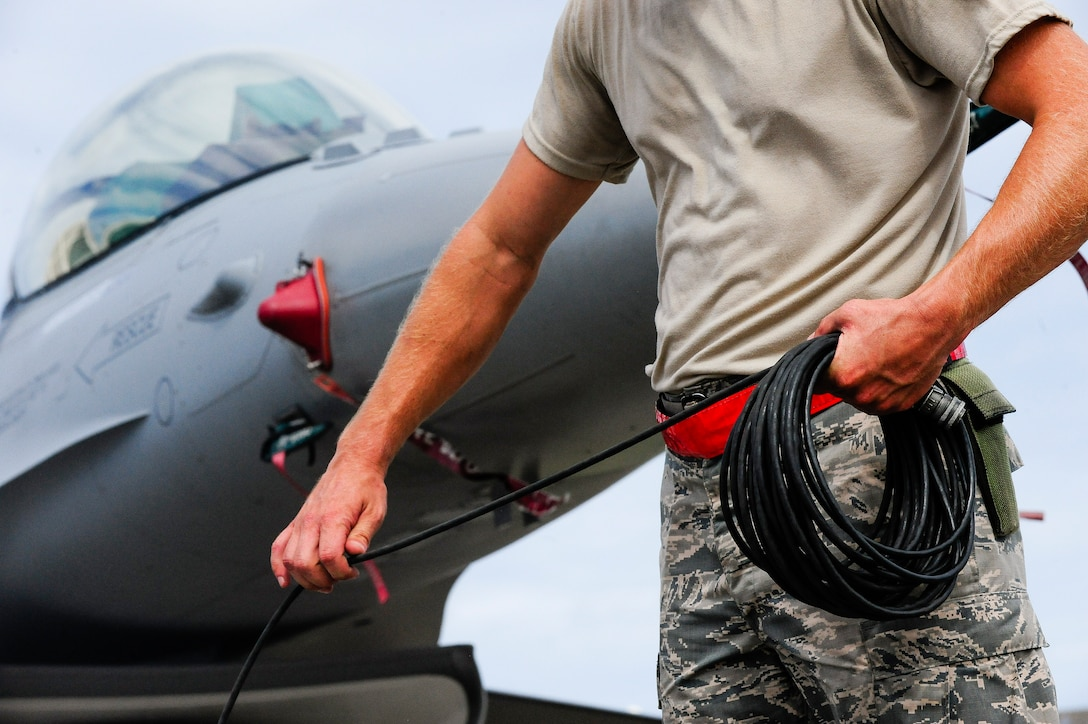 U.S. Air Force Master Sgt. David Custer, Vermont Air National Guard's 158th Maintenance Squadron lead crew chief, coils up a communication wire in front of a U.S. Air Force F-16 Fighting Falcon on Kadena Air Base, Japan, July 22, 2015. The F-16 is a compact, multi-role fighter aircraft. The 158th ANG Fighter Wing is temporarily deployed to Kadena to provide a theater security package throughout the Indo-Asia-Pacific region. (U.S. Air Force photo by Airman 1st Class John Linzmeier)