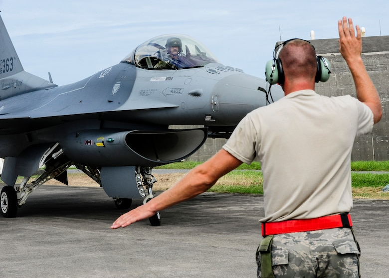 U.S. Air Force Master Sgt. David Custer, Vermont Air National Guard's 158th Maintenance Squadron lead crew chief, martials a U.S. Air Force F-16 Fighting Falcon into its parking space on Kadena Air Base, Japan, July, 22, 2015. The 158th ANG Fighter Wing is providing a theater security package throughout the Indo-Asia-Pacific region. (U.S. Air Force photo by Airman 1st Class John Linzmeier)
