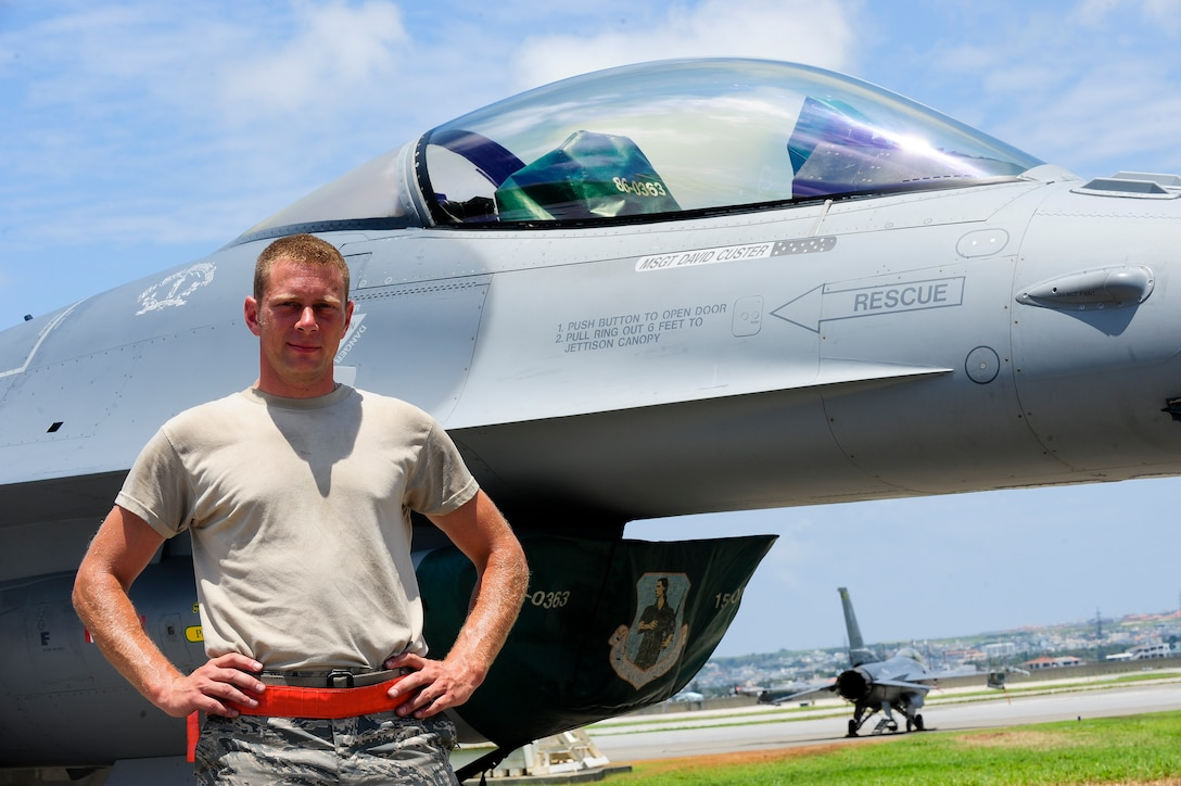 U.S. Air Force Master Sgt. David Custer, Vermont Air National Guard's 158th Maintenance Squadron lead crew chief, stands in front of a U.S. Air Force F-16 Fighting Falcon July, 16, 2015, on Kadena Air Base, Japan. His name can be found printed on the right side of the aircraft as he is held responsible for ensuring the jet is properly maintained. The 158th ANG Fighter Wing is providing a theater security package throughout the Indo-Asia-Pacific region. (U.S. Air Force photo by Airman 1st Class John Linzmeier)