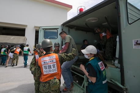 """Members of the Japan Ground Self Defense Force and Japan Disaster Medical Assistance Team assist a role player off an ambulance July 23, during the Churashima Rescue Exercise on Camp Naha, Okinawa, Japan. The annual exercise hosted by the 15th Brigade, Western Army, Japan Ground Self Defense Force, trains emergency responders for a swift reaction to the disaster effects of a trench-type earthquake. """"In close cooperation with prefectural disaster response organizations, both civilian and defense, we practiced how information is shared, where we need to improve, and what we can accomplish next time more fully,"""" said Japan Ground Self Defense Force Lieutenant Colonel  Naruhito Seo, 15th Brigade Headquarters. (U.S. Marine Corps photo by Lance Cpl. Daniel Jean-Paul/Released)"""