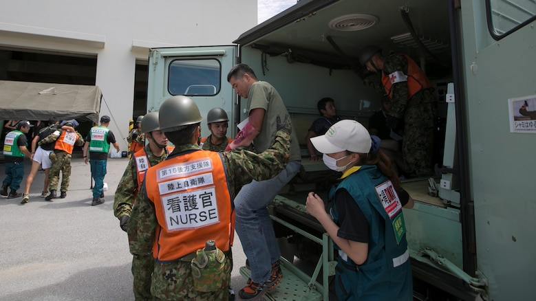"Members of the Japan Ground Self Defense Force and Japan Disaster Medical Assistance Team assist a role player off an ambulance July 23, during the Churashima Rescue Exercise on Camp Naha, Okinawa, Japan. The annual exercise hosted by the 15th Brigade, Western Army, Japan Ground Self Defense Force, trains emergency responders for a swift reaction to the disaster effects of a trench-type earthquake. ""In close cooperation with prefectural disaster response organizations, both civilian and defense, we practiced how information is shared, where we need to improve, and what we can accomplish next time more fully,"" said Japan Ground Self Defense Force Lieutenant Colonel Naruhito Seo, 15th Brigade Headquarters."