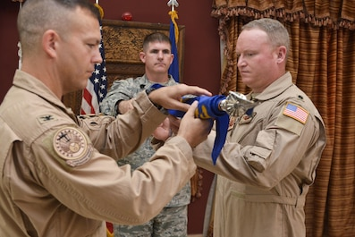 Col. James Dittus, 379th Expeditionary Operations Group commander and Lt. Col Ronald Schochenmaier, 22d Expeditionary Air Refueling Squadron commander, unveil the squadron flag during an assumption of command ceremony for the 22d EARS July 24th 2015 at Al Udeid Air Base, Qatar. The 22d was first formed in 1939 primarily as a bomb squadron for World War II. In 2002 it was inactivated as the 22d Air Refueling Squadron and is now re-designated as the 22d EARS supporting operations from Al Udeid Air Base. (U.S. Air Force photo/Staff Sgt. Alexandre Montes)