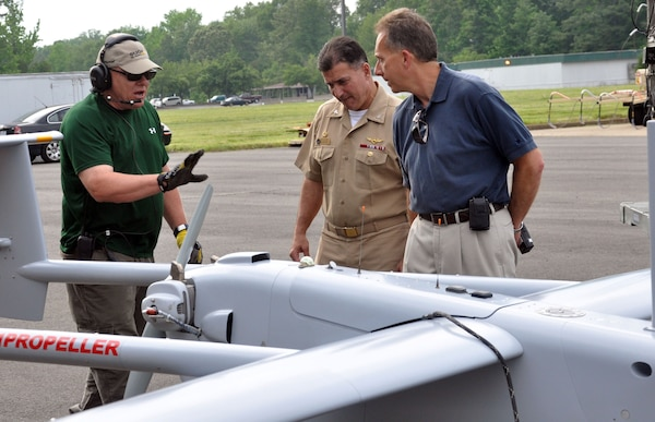 Donn Rushing, left, crew chief for the Unmanned Aerial Systems Test Directorate, briefs Capt. Pete Nette, center, commanding officer of Naval Support Activity South Potomac, and Nelson Mills, right, senior engineer at the Naval Surface Warfare Center Dahlgren Division, about the Aerostar UAS in the foreground during testing May 21. The planning phase of the test required extensive coordination with between Dahlgren-based commands, Naval Air Systems Command and the FAA.