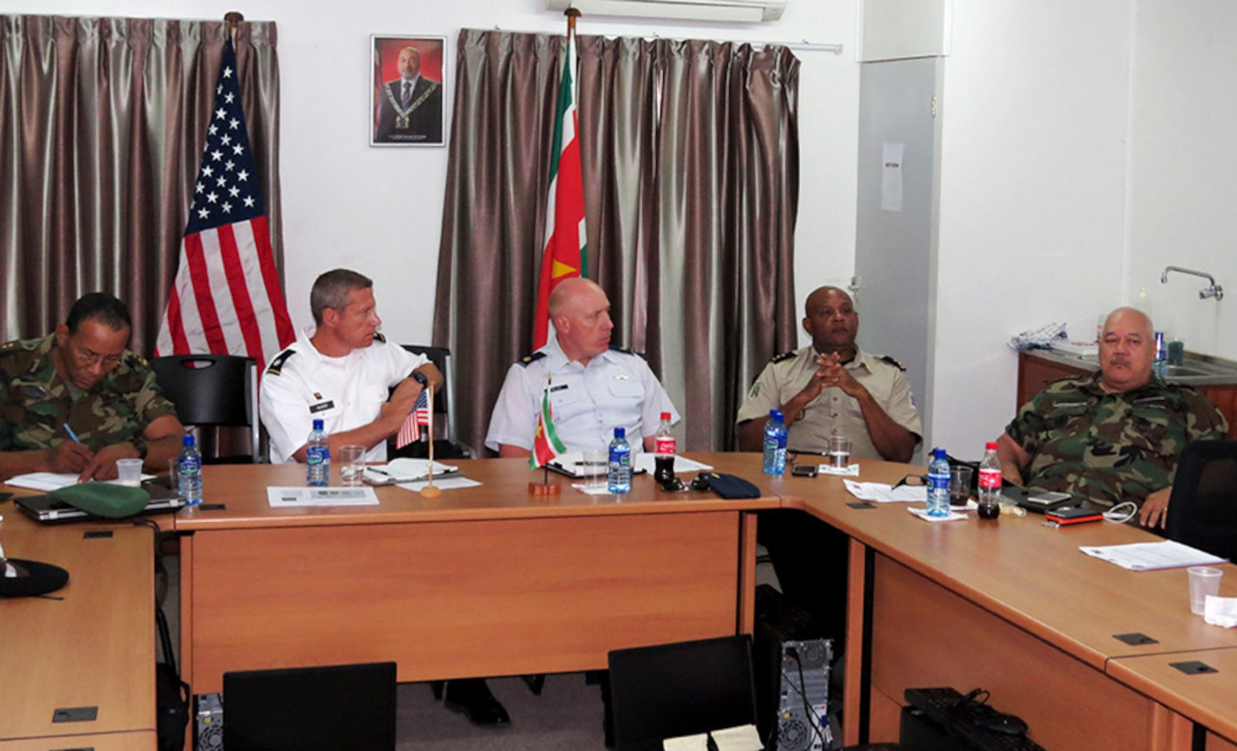 U.S. Army Lt. Col. Orson Ward, second from left, South Dakota Army National Guard, and U.S. Air Force Maj. Kevin Miller, center, South Dakota Air National Guard, participate in a subject matter expert exchange on strategic planning in Paramaribo, Suriname, July 15, 2015.