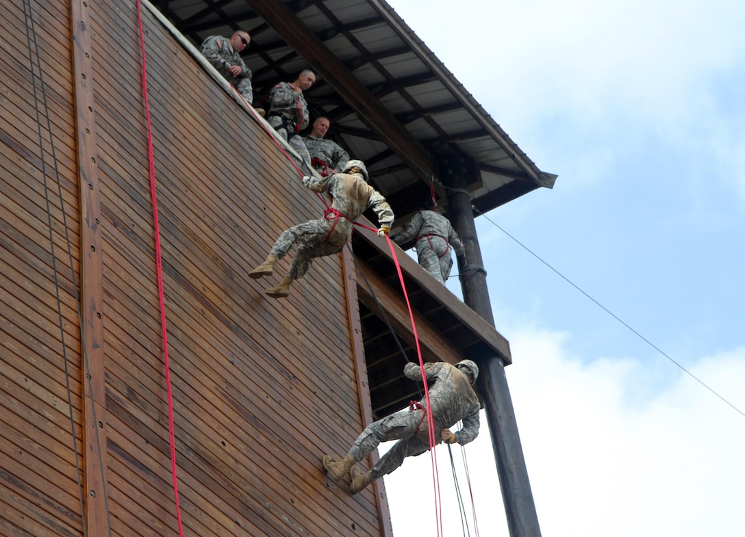 Cadets of the 7th Regiment, Combat Leader Course negotiate the rapelling tower Saturday, July 11 at Fort Knox, Ky. The rappelling tower exercise is used to help cadets overcome fear, instill them with confidence and to build empathy for their subordinates in challenging circumstances. (U.S. Army Photo by Sgt. Javier Amador)