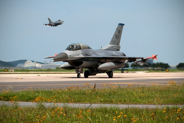 A U.S. Air Force 35th Fighter Squadron F-16 Fighting Falcon taxis on the Kunsan Air Base runway as an 80th Fighter Squadron F-16 Fighting Falcon takes off during Exercise Buddy Wing 15-4 at Kunsan Air Base, Republic of Korea, July 16, 2015. The five-day quarterly operational readiness exercise enhanced strategic capabilities at Kunsan by generating combat airpower in a simulated chemical, biological, radiological, nuclear and high-yield explosive environment. (U.S. Air Force photo by Senior Airman Katrina Heikkinen/Released)